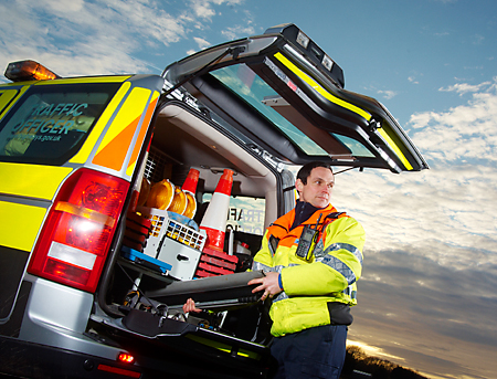 Traffic Officer unpacks equipment from his vehicle whilst keeping a watchful eye on the oncoming traffic